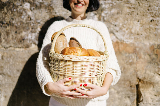 Cheerful woman with bread near wall