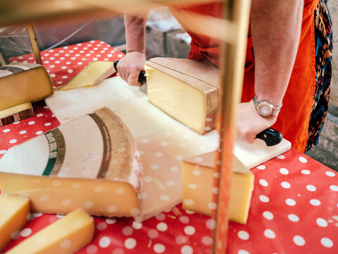 A farmer cutting cheese at the market in Beaune, Burgundy, France