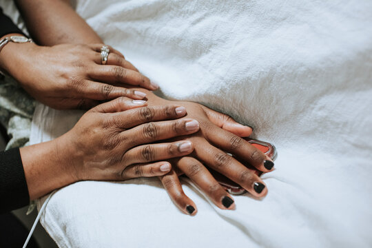 Closeup of Hands as Mother Comforts Daughter in Hospital Bed
