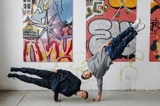 Dancers making tricks near graffiti wall.