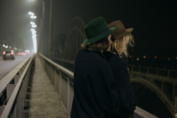 a couple in suits and hats stands on the bridge Fotomurales