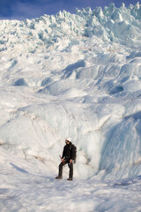 A man in equipment stands on the background of a glacier