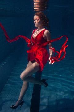 beautiful woman wearing red dress underwater, strange and artistic