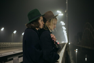 two guys in a coat hugged on the bridge in the evening Fotomurales