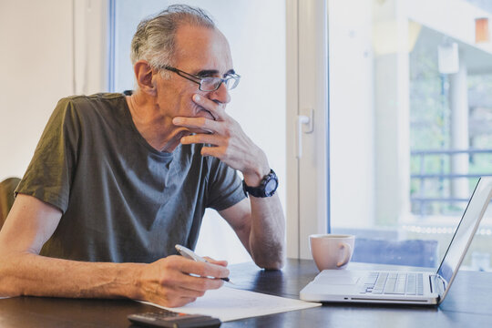 elderly senior man working on laptop computer at home, looking at screen and thinking