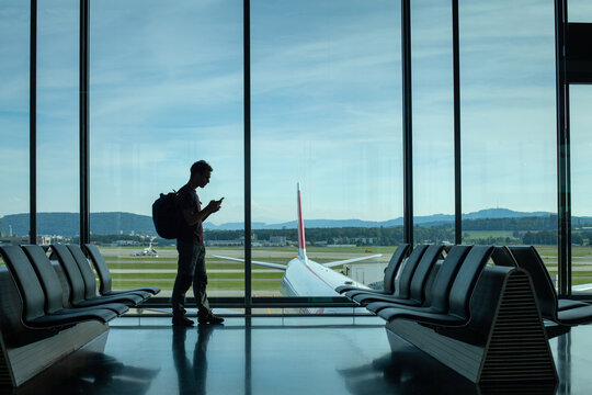 passenger using phone in airport, silhouette of man waiting for departure