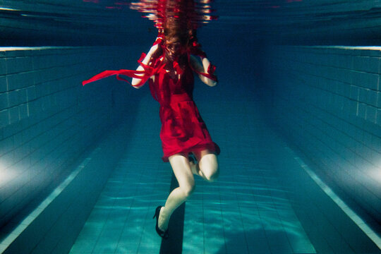 blurry woman wearing red dress underwater, strange and artistic, motion blur