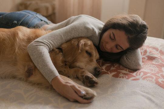 girl carefully hugs a sick lying dog