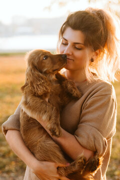 Young girl kissing dog outdoor