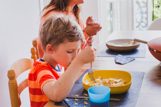 child eating pasta with fork at the table for dinner with his family