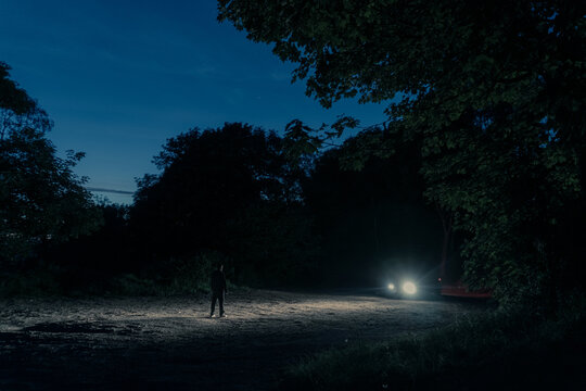 A mysterious figure silhouetted against car headlights at night