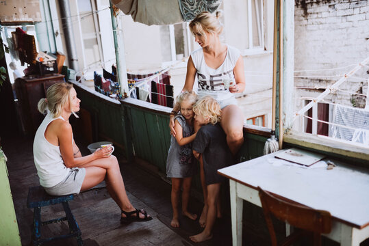 Two women with children talking on the balcony