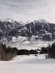 A view on a skiing slope and mountains range in a distance