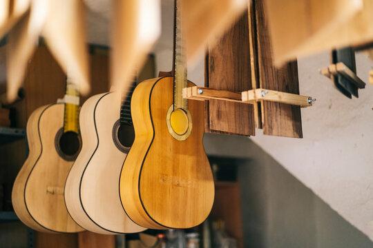 Guitars hanging in a line at workshop