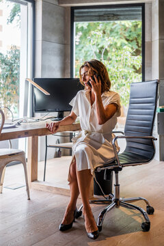 Businesswoman talking on phone while sitting by desk at office