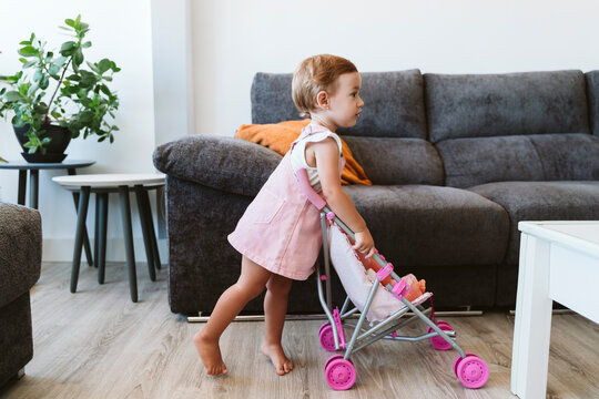 Baby girl playing with toys and baby stroller at home