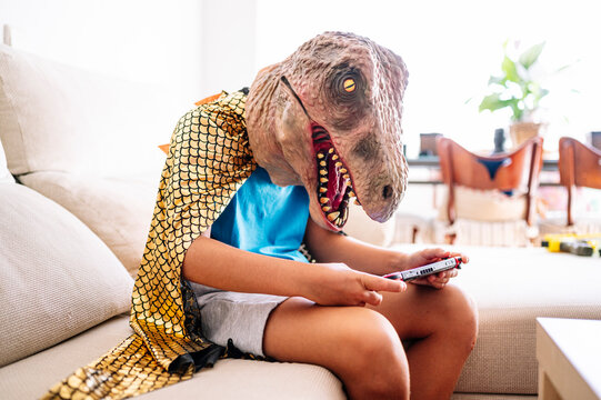 Boy wearing dinosaur mask and cape using smart phone while sitting on sofa at home