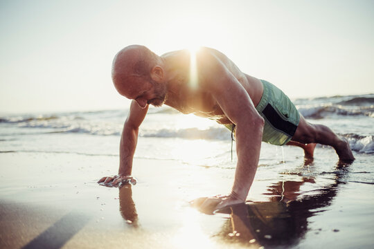Senior man exercising at beach during sunset