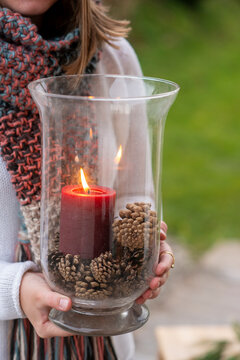 Close-up of young woman holding container with candle and pine cones while standing outdoors