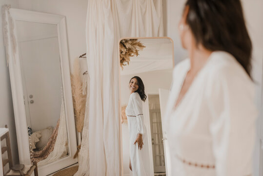 Young bride looking in mirror while standing at home