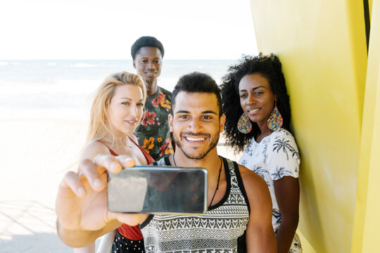 Friends taking selfie while standing in lifeguard hut at beach