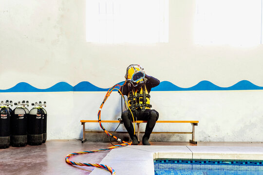 Man wearing diving suit while sitting on bench against wall at poolside