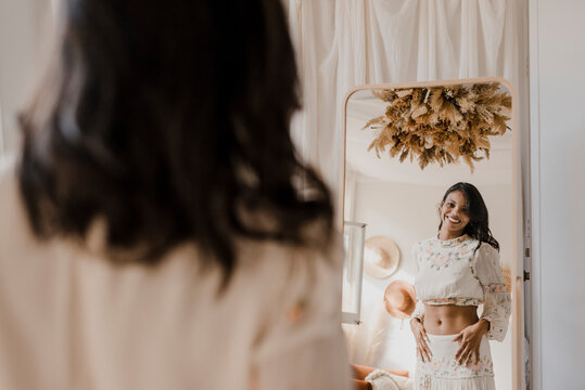 Reflecting image of smiling bride looking in mirror at home