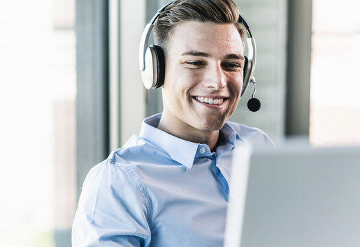 Close-up of smiling businessman talking over headset in call center