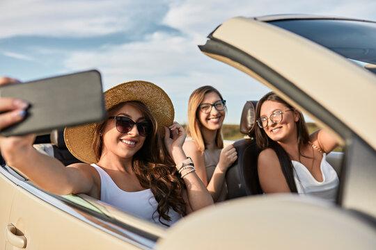 Friends taking selfie on smart phone while enjoying road trip sitting in luxury car