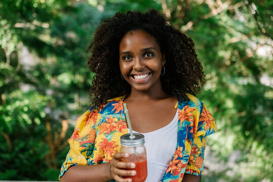 Smiling young woman holding juice while standing in park