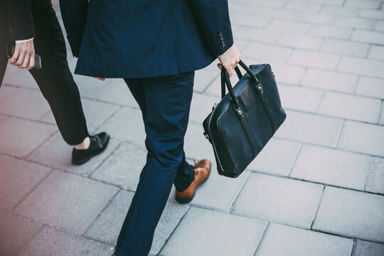 Low section of business colleagues walking on sidewalk