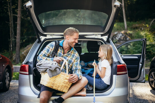 Smiling father with picnic basket talking to daughter while sitting in car trunk