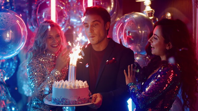 Charming guy and girls standing with cake in club. Man blowing candles at party