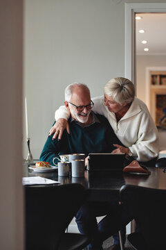 Smiling senior couple talking by dining table in living room