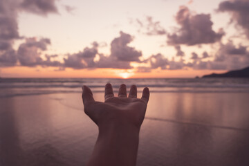 Woman hand reach out to sunset beach.