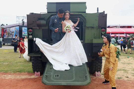 A couple takes wedding photos on a Taiwan Infantry Fighting Vehicle during a military mass wedding in Taoyuan