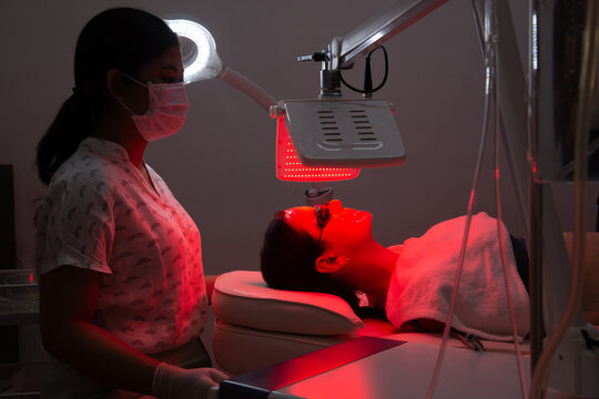 Young woman having red LED light facial therapy treatment in beauty salon. Beautician wearing face mask maintaining safety procedures during appointment. Beauty, new normal and wellness