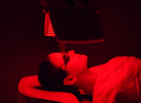 Young woman having red LED light facial therapy treatment in beauty salon. Beauty and wellness