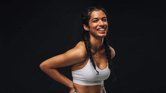 Smiling fit woman on black background