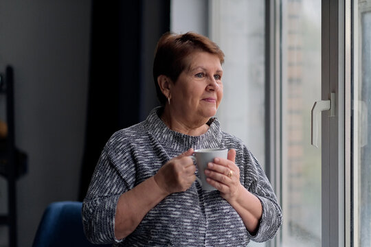 Portrait of senior woman with cup of coffee looking out of window. Elegant mature lady drinking hot coffee and relaxing near window smiling and dreaming indoors.
