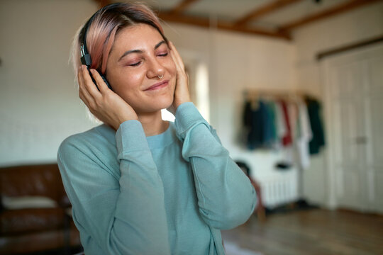 Beautiful 20 year old young woman with pinkish hair and nose piercing keeping eyes closed and smiling happily, enjoying music via mp3 player, using her new wireless headphones, posing at home