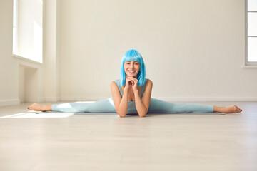 Positive yoga or gymnastics trainer doing straddle side splits lying on gym floor