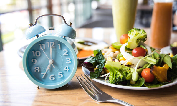 Selective focus with Blue clock breakfast time and Intermittent fasting ,Lifestyle concept.