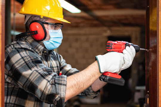 Carpenter worker at work repairs and installs a room door, wear the surgical mask to prevent Coronavirus infection. Preventing Pandemic Covid-19 at the workplace. Carpentry.