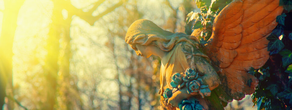 Antique statue of gold angel in rays of hope and sun. Metaphor image.
