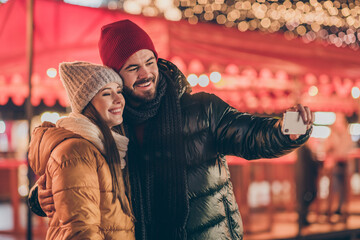 Photo of two people students couple make selfie on cellphone x-mas christmas street event under outside advent lights Fotomurales