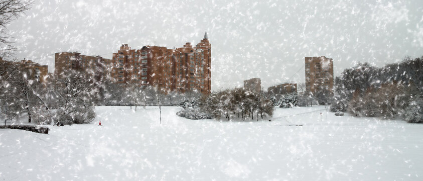 image of a heavy snowfall. Blizzard and snowstorm in the city on a frozen pond. Residential buildings on the Bank of an ice-bound river. A Blizzard with strong winds hits the city.