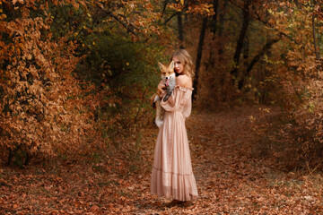 Model in a dress with a red fox in the autumn forest