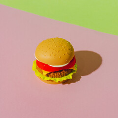 Appetizing burger with shadow on green and pink background. Creative concept. Plastic pop art...