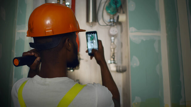 Back view of african engineer with flashlight taking photo on smartphone of broken heating system